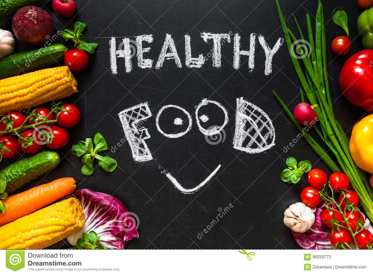 Healthy food concept with fresh vegetables for cooking.Title `Healthy food` with smile is written by chalk on the background
