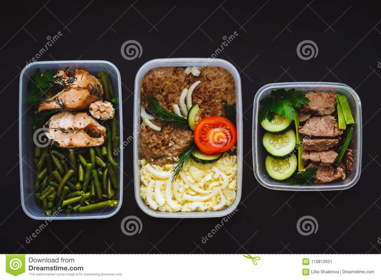 The healthy food in the containers on black background: snack, dinner, lunch. Baked fish, beans, beef cutlets, mashed potatoes, me