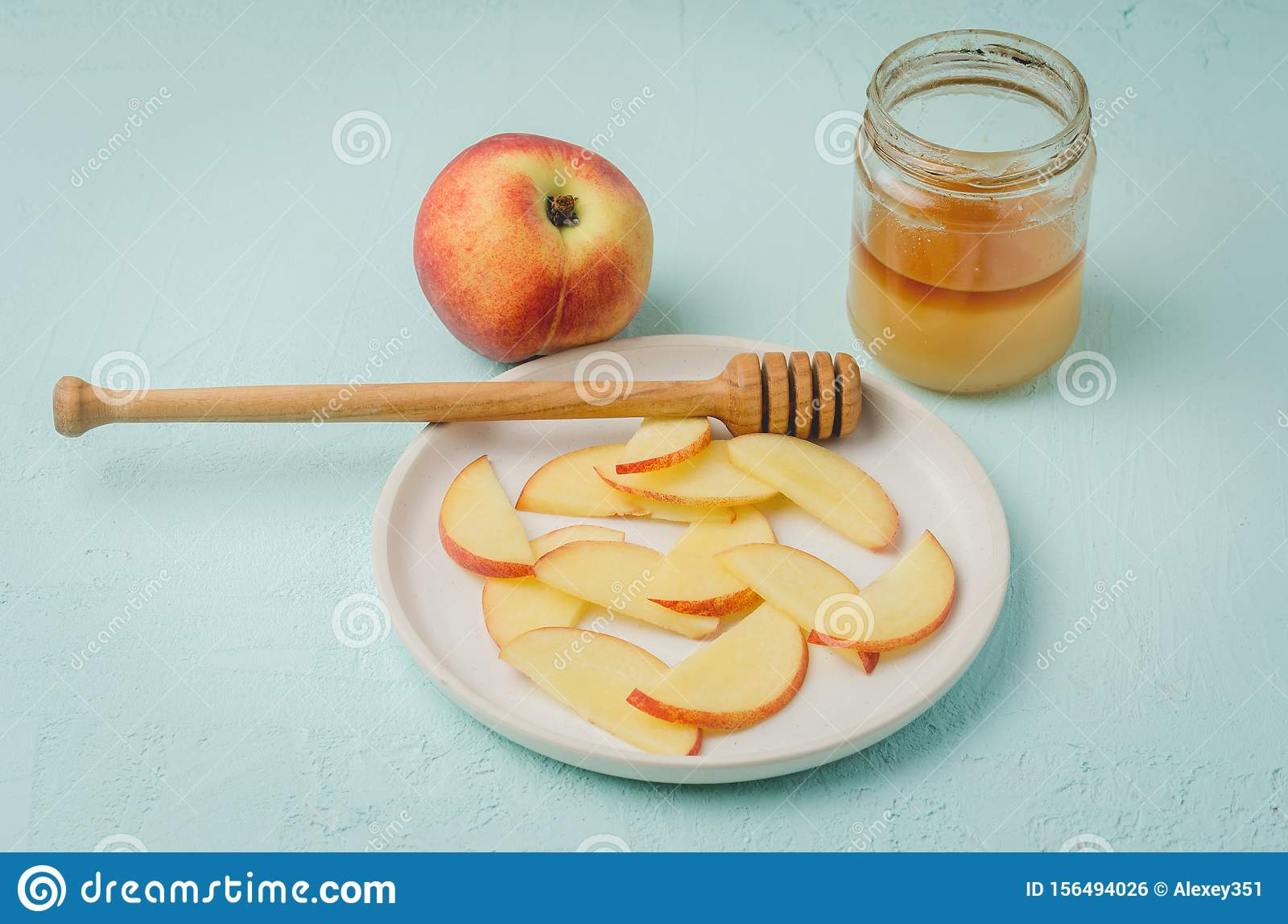 Healthy food. Sliced peach with honey in a bowl, selective focus. Blue background