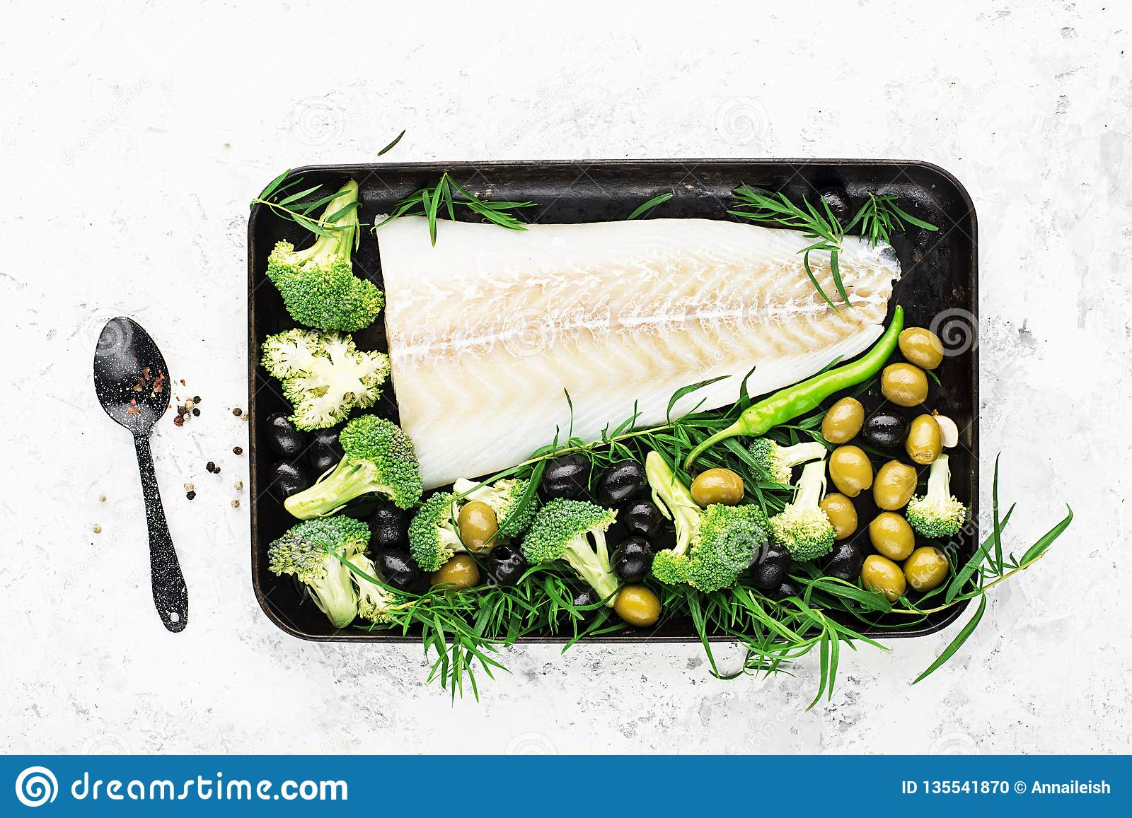 Healthy food: wild organic fresh sea white cod fish with broccoli, tarragon, onions, olives on a baking sheet. The