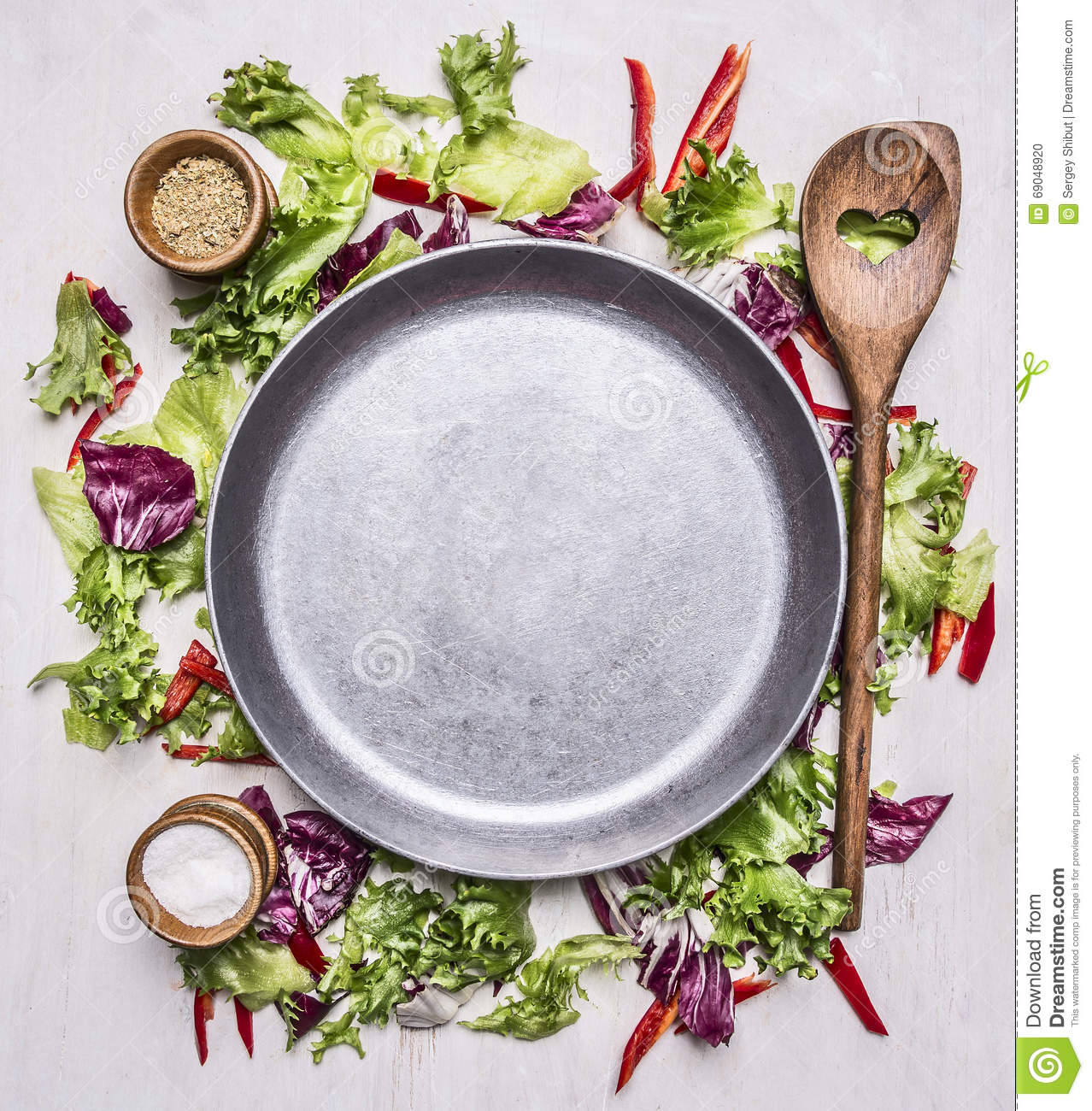 Healthy foods, cooking and vegetarian concept lettuce with a wooden spoon, salt and pepper, laid out around pan place for text