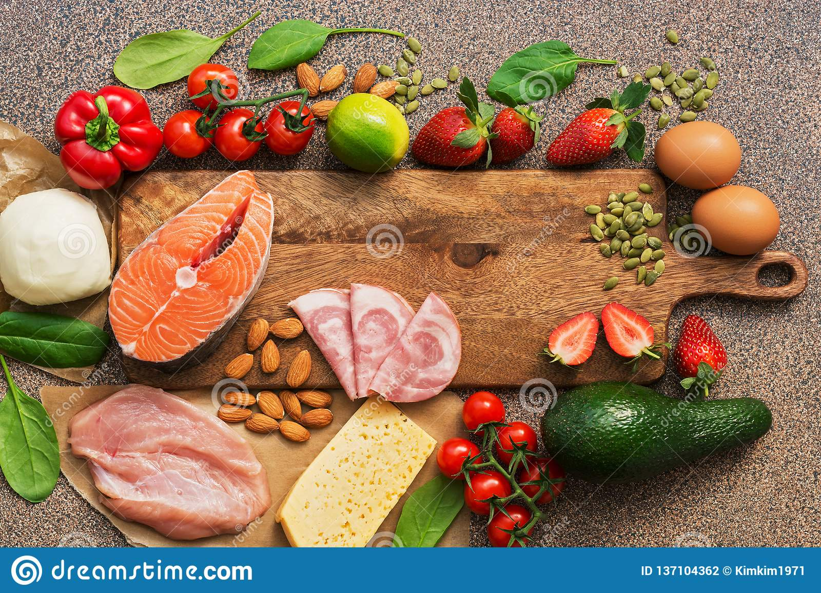 Healthy foods low in carbohydrates. Keto diet concept. Salmon, chicken, vegetables, strawberries, nuts, eggs and tomatoes, cutting