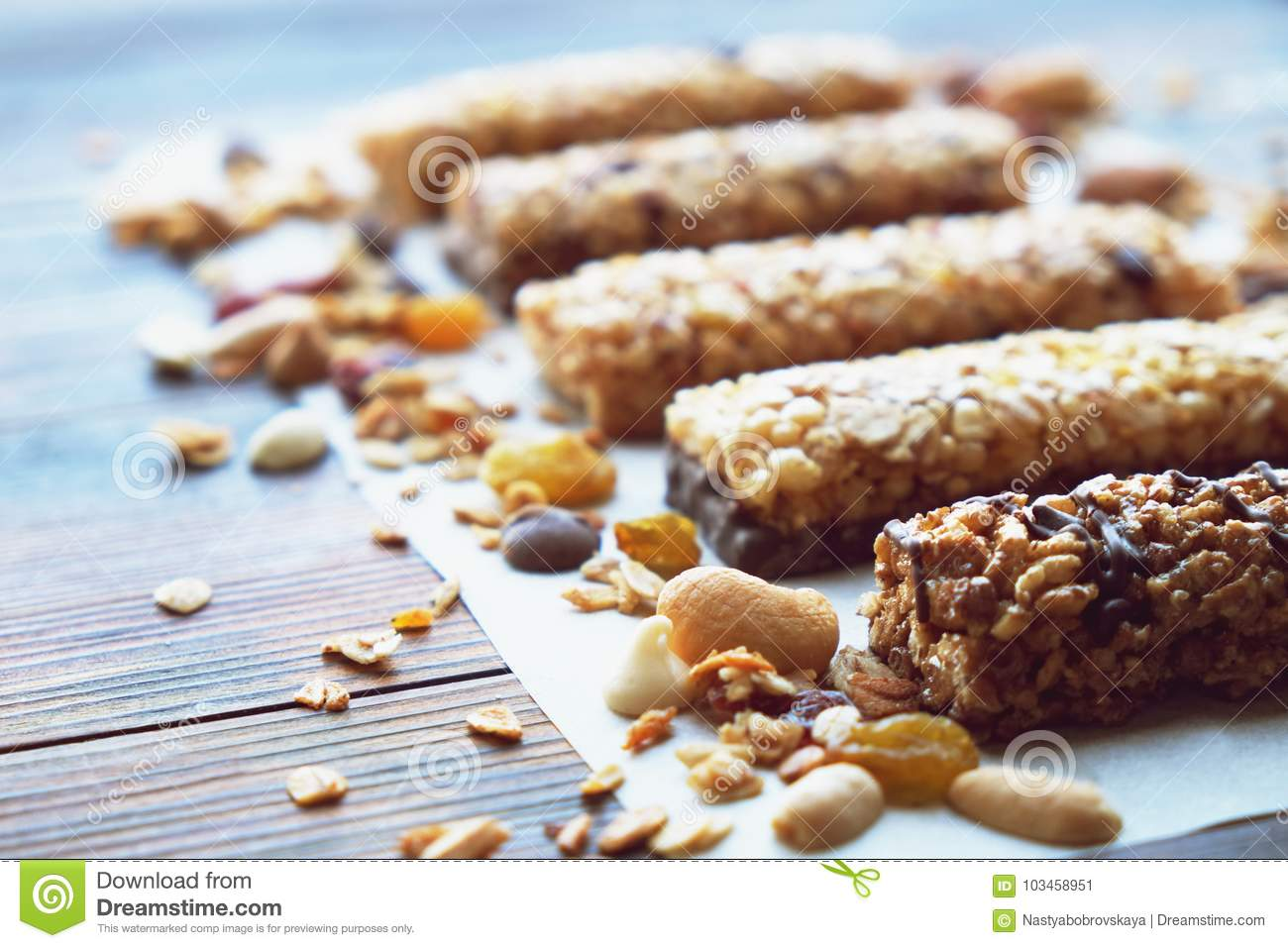 Healthy granola bars with dried fruits, nuts and honey on wooden background.