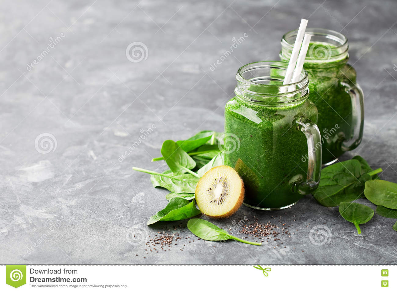 Healthy green smoothie with spinach, kiwi and chia seeds in a jar mug ...