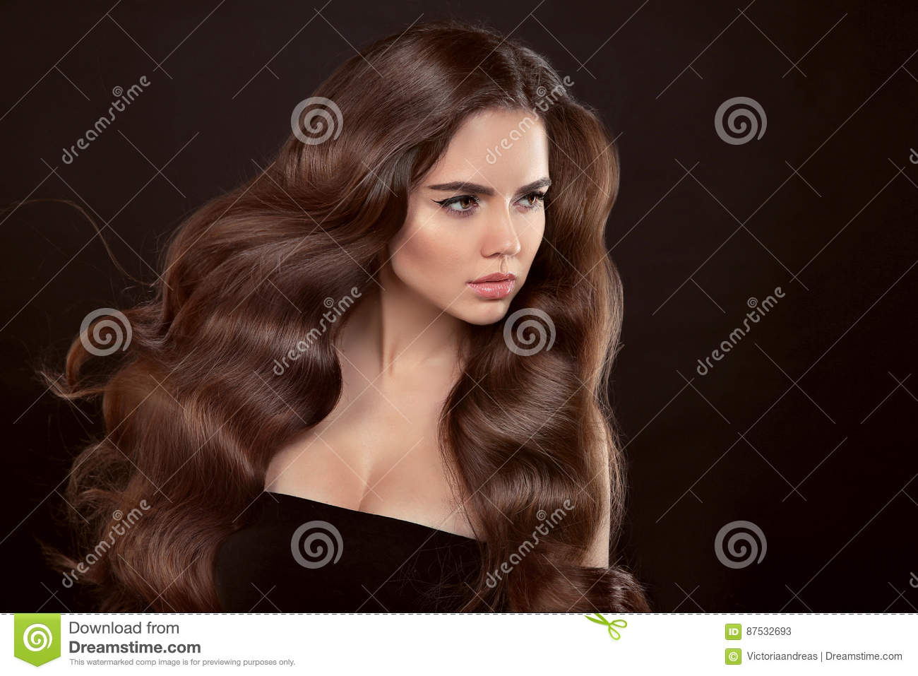 Healthy hair. Wavy hairstyle. Beautiful brunette woman with clean skin and shiny brown straight long hair isolated on black