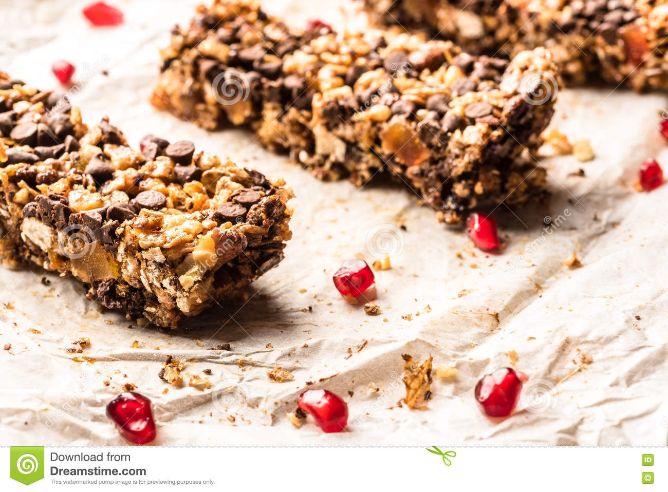Healthy homemade muesli bar with cereal, chocolate and pomegranate and copyspace