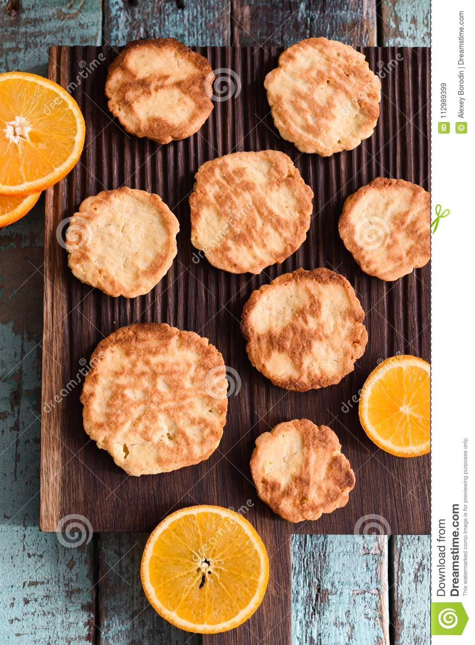 Healthy homemade sweets. Cookies and orange slices on oak cutting board on shabby blue background