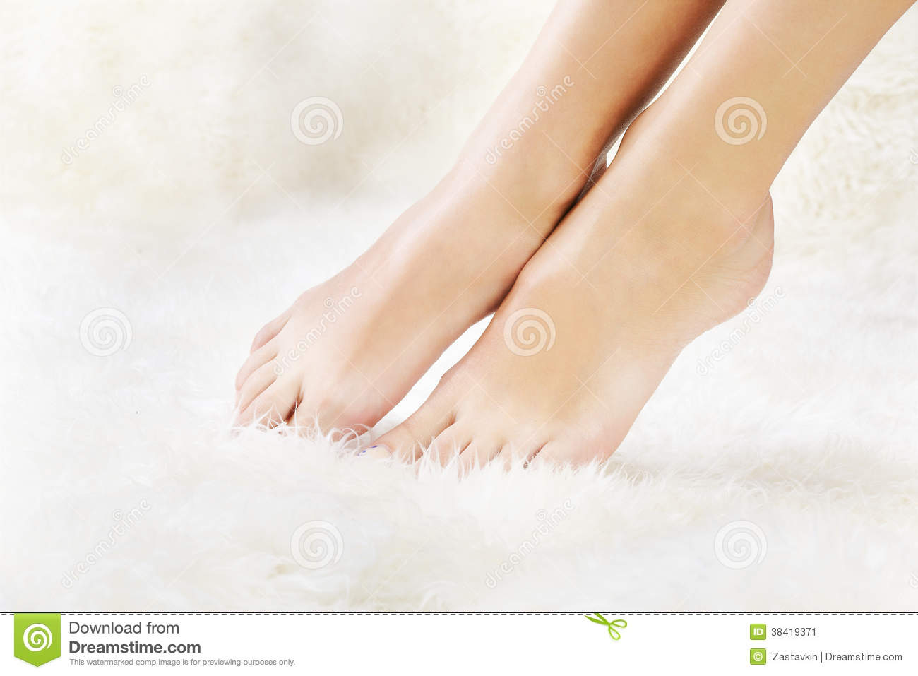 Body part shot of beautiful healthy young woman s legs on white fur