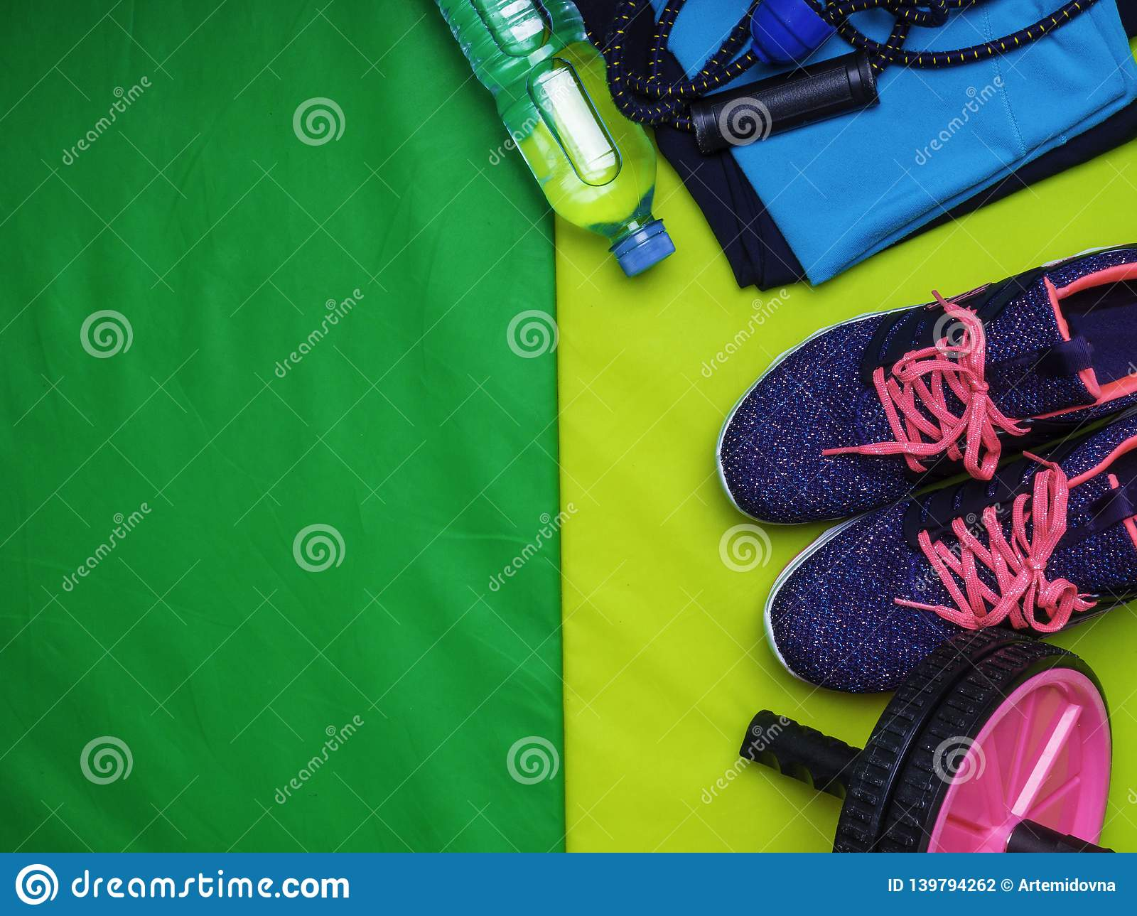 1322c154b95c8 Healthy lifestyle background. Green mat, sport shoes, bottle of water,  expander, the press wheel Concept healthy and sport life.