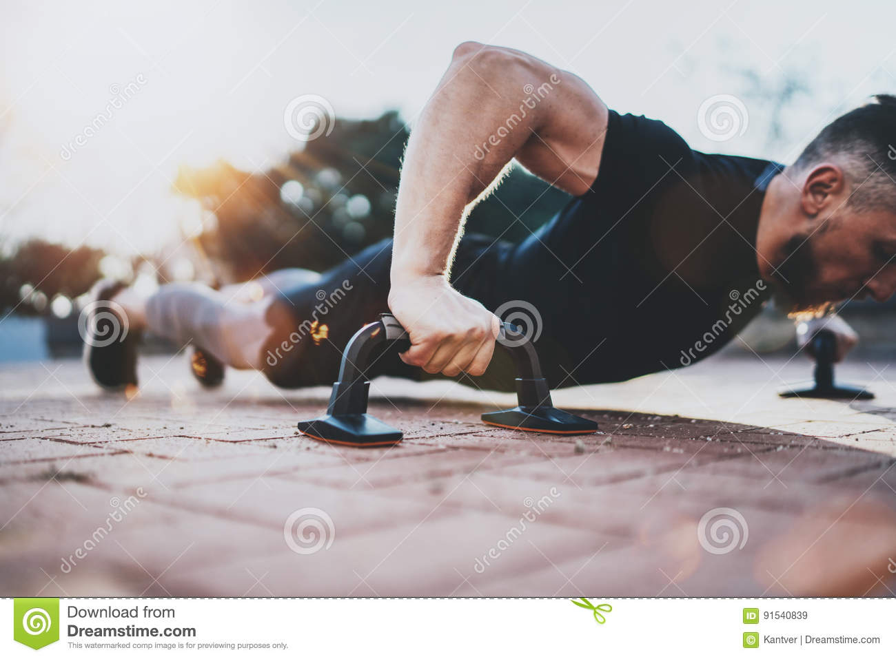 Healthy lifestyle concept.Training outdoors.Handsome sport athlete man doing pushups in the park on the sunny morning