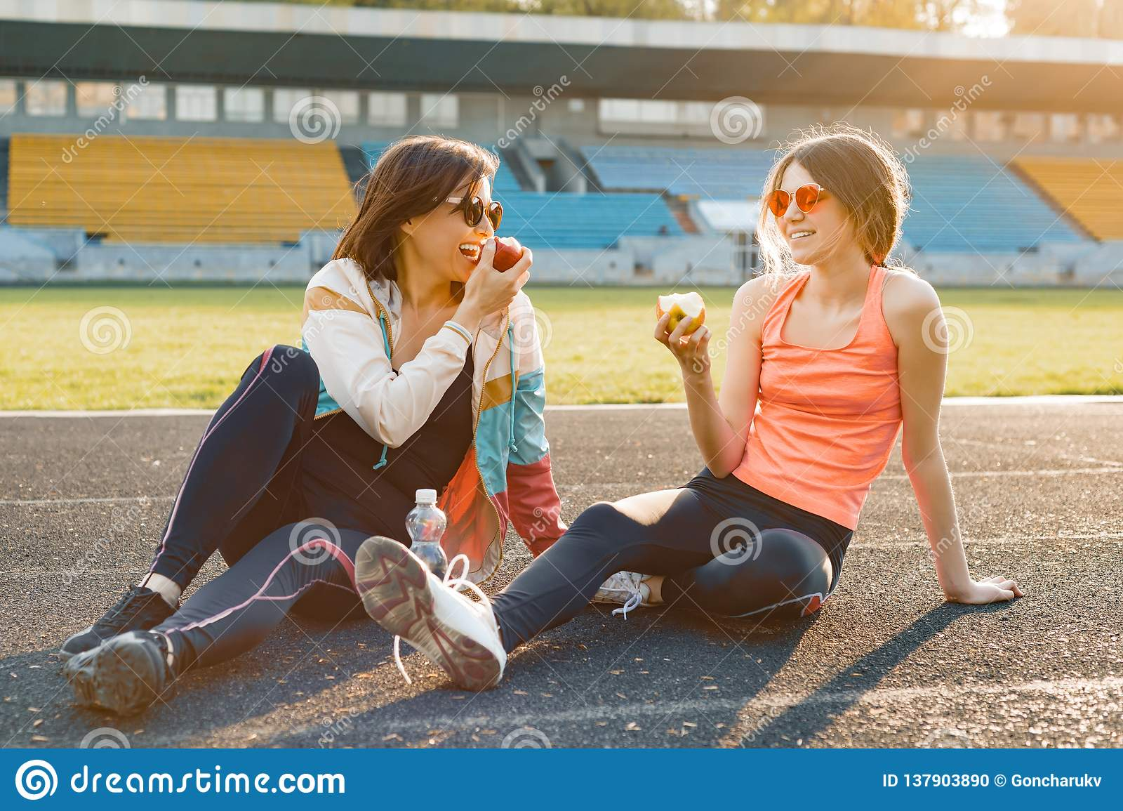 Healthy lifestyle and healthy food concept. Smiling fitness mother and teen daughter together eating apple sitting on stadium