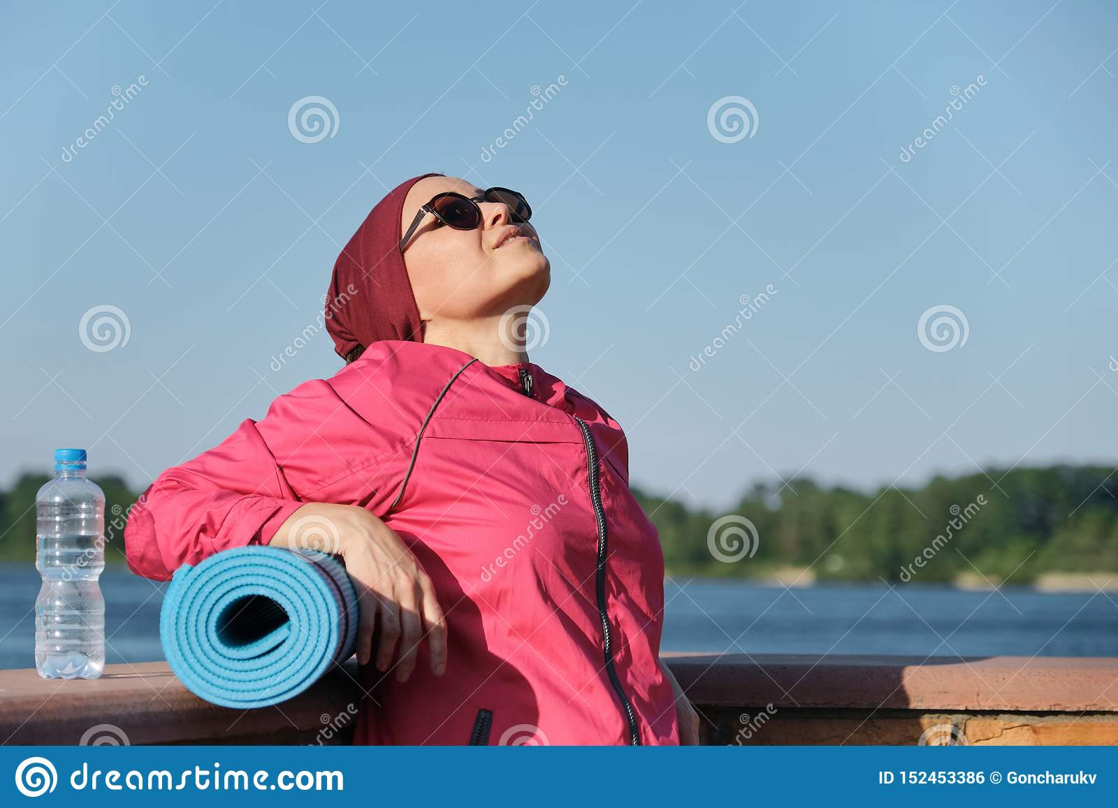 Healthy lifestyle of mature woman, outdoor portrait of an age female in sportswear with yoga mat and bottle of water