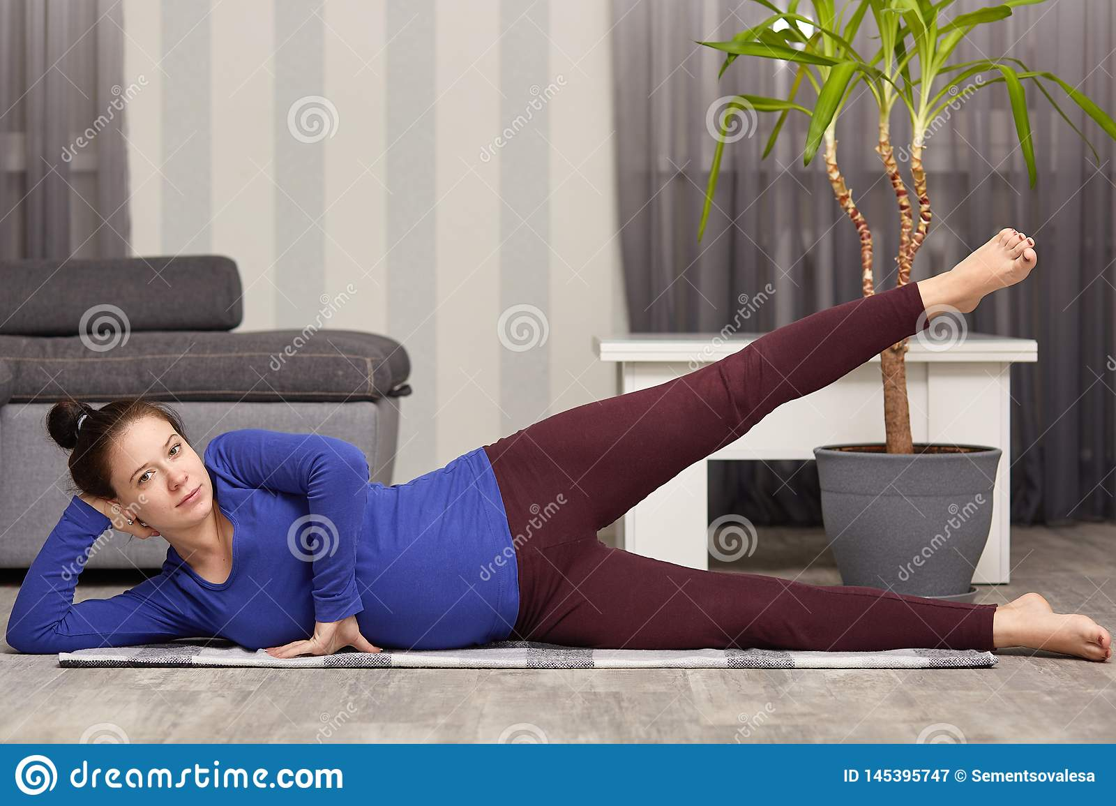 Healthy lifestyle during pregnancy. Pregnant woman lies on her hip and lifting her leg, has dark hair combed in knot, models