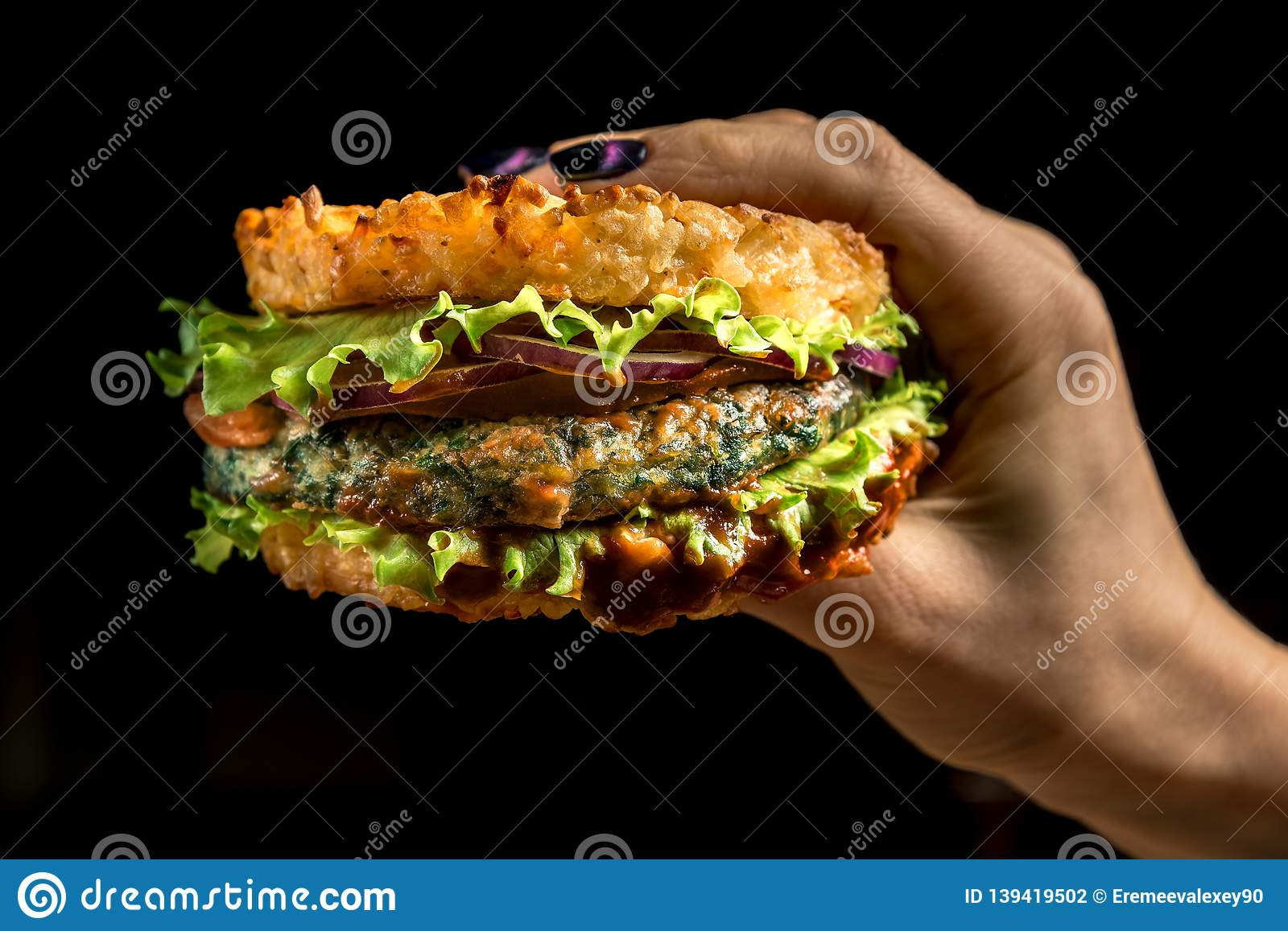 Healthy lifestyle, proper nutrition. Healthy rice burger with vegetables, herbs and cutlet in female hands
