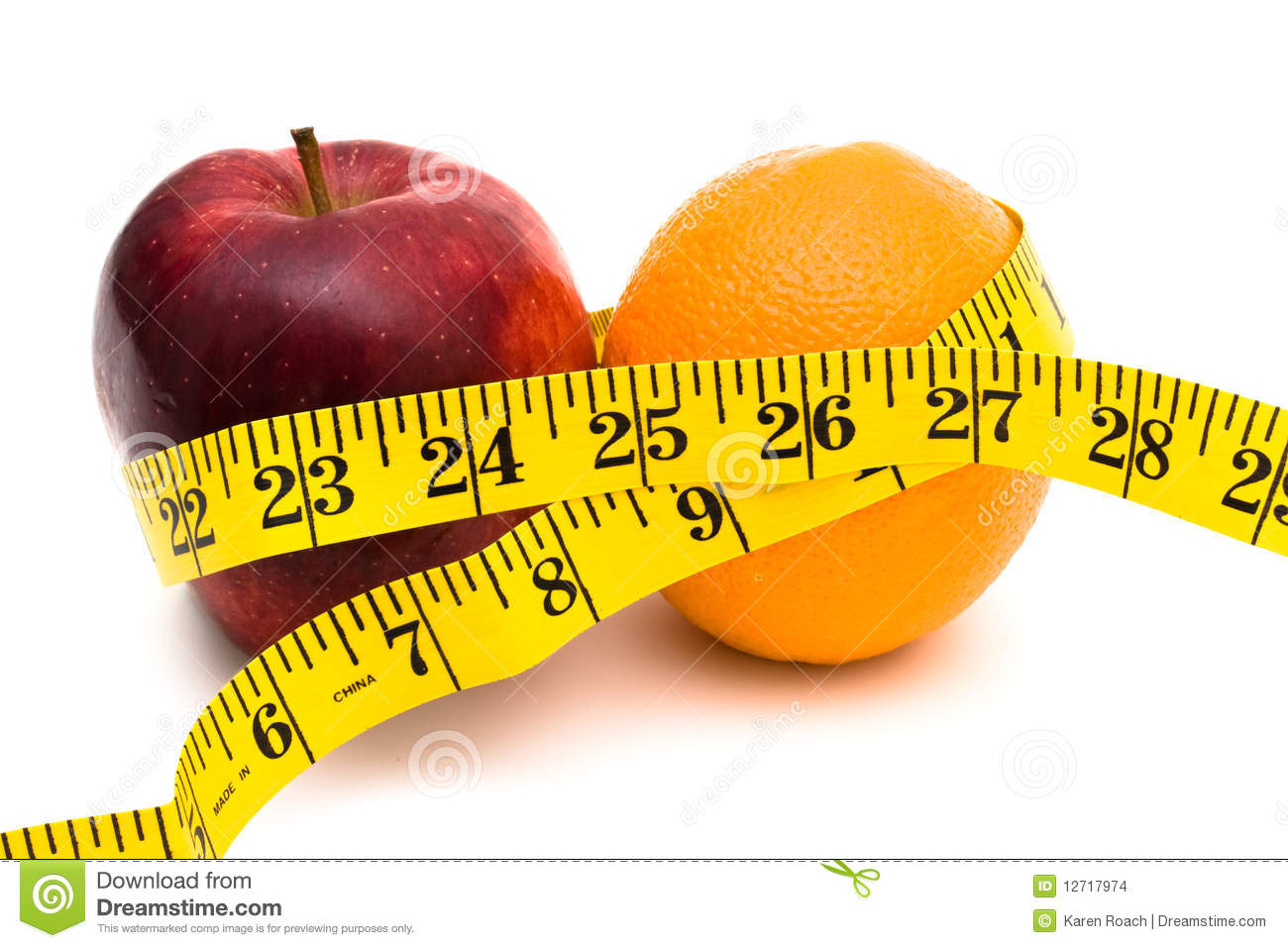 An apple and an orange with a measuring tape on a white background ...