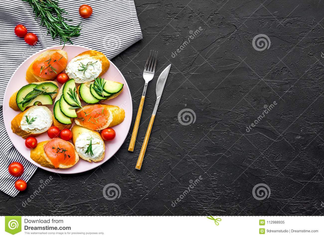 Healthy lunch with mini sandwiches cheese, fish and avocado on black background top view space for text