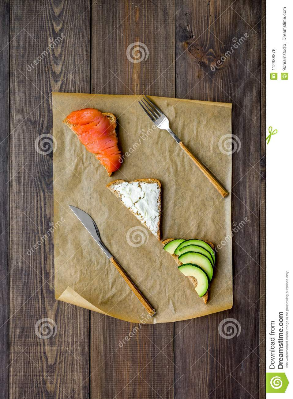 Healthy lunch with mini sandwiches cheese, fish and avocado on wooden background top view space for text