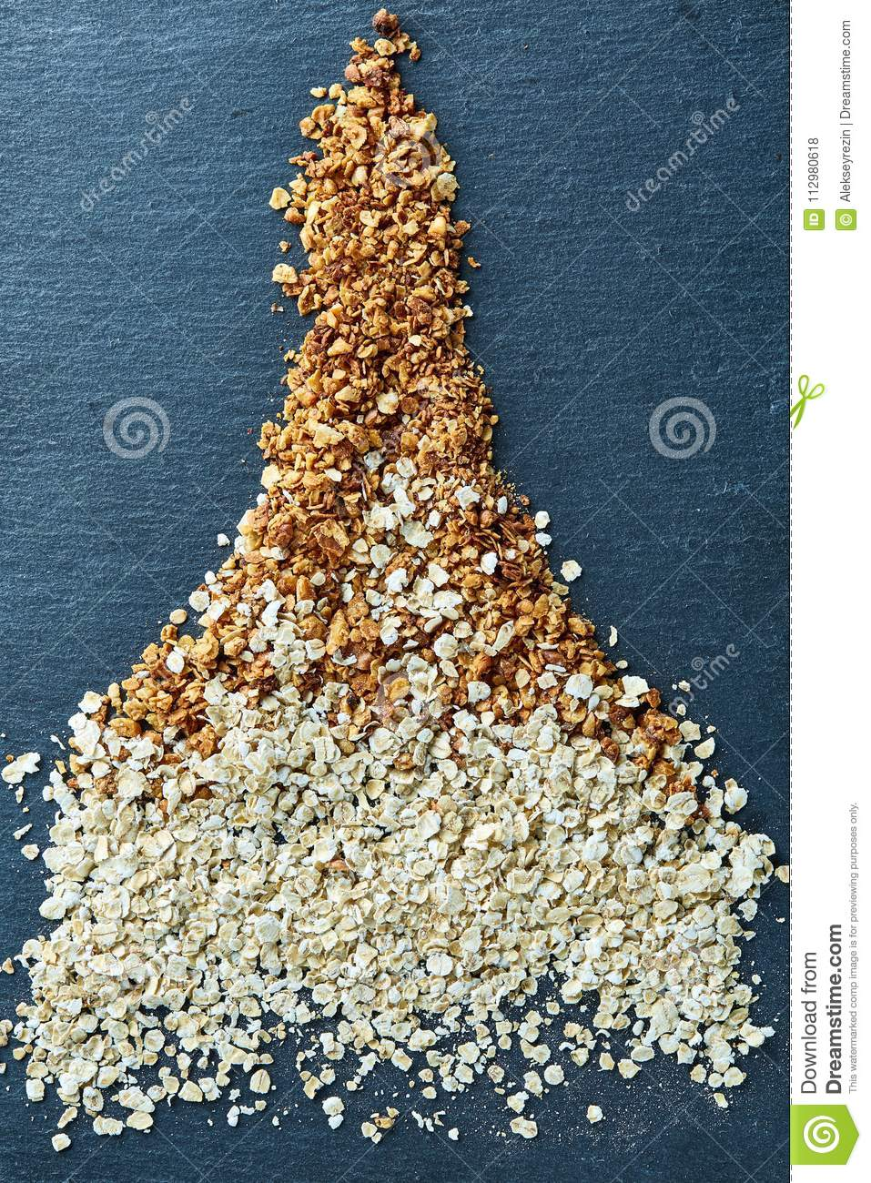 Healthy mix of granola and oatmeal on dark board over wooden background, top view, close-up, selective focus