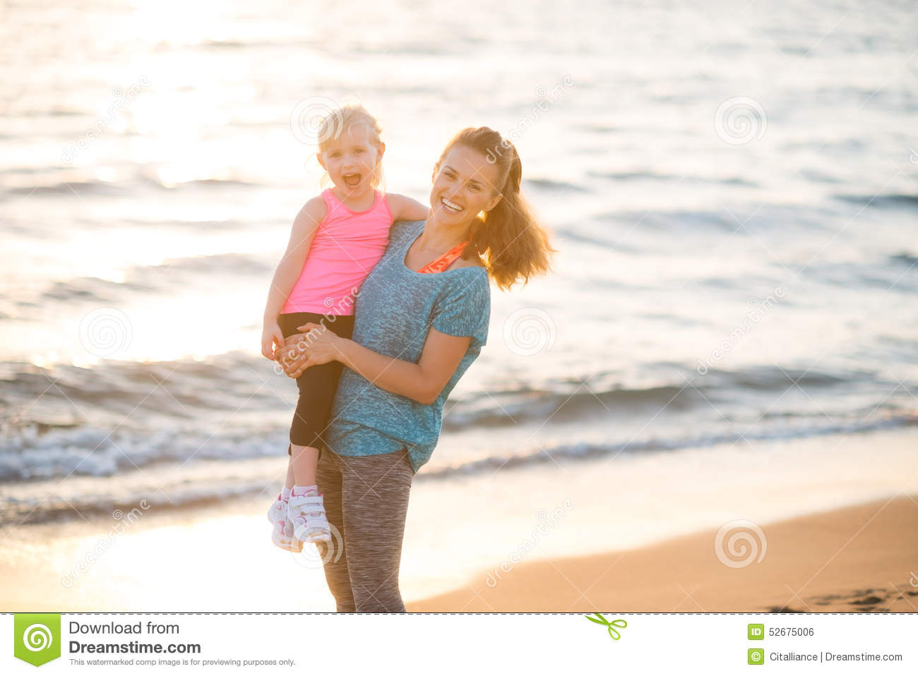 Healthy mother and baby girl on beach