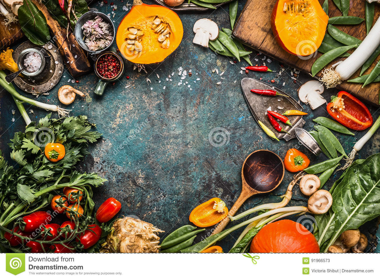 Healthy and organic harvest vegetables and ingredients: pumpkin, greens, tomatoes,kale,leek,chard,celery on rustic kitchen table b