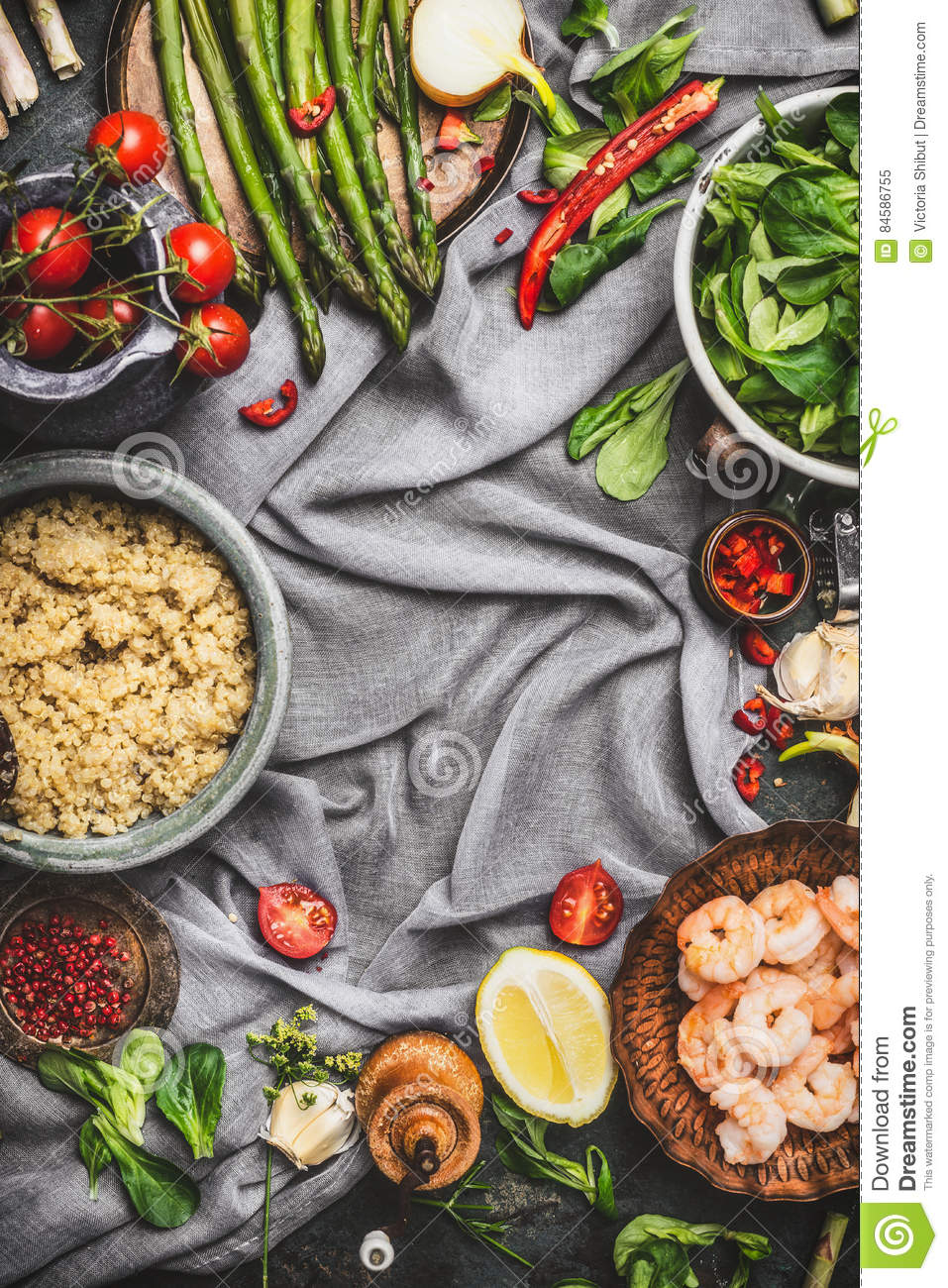Healthy salad with asparagus and cooked quinoa seeds, preparation on rustic background with various organic vegetables, top view,