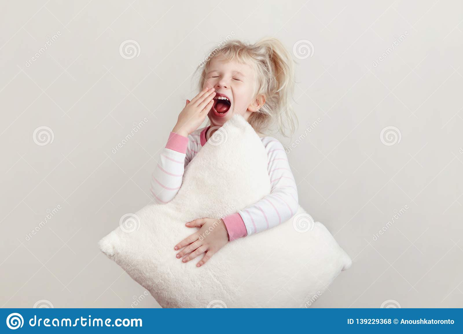 934cf1c072 Cute blonde Caucasian girl child in pink pajamas with closed eyes yawning  covering wide open mouth with palm. Sleepy kid with messy hair holding  white soft ...