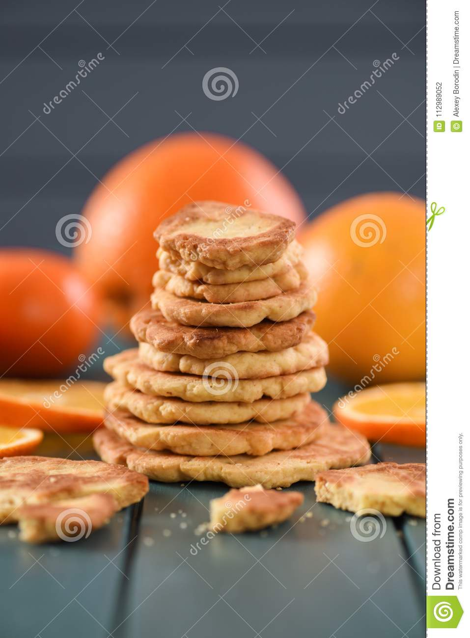 Healthy snack. Pile of homemade cookies and oranges on dark blue