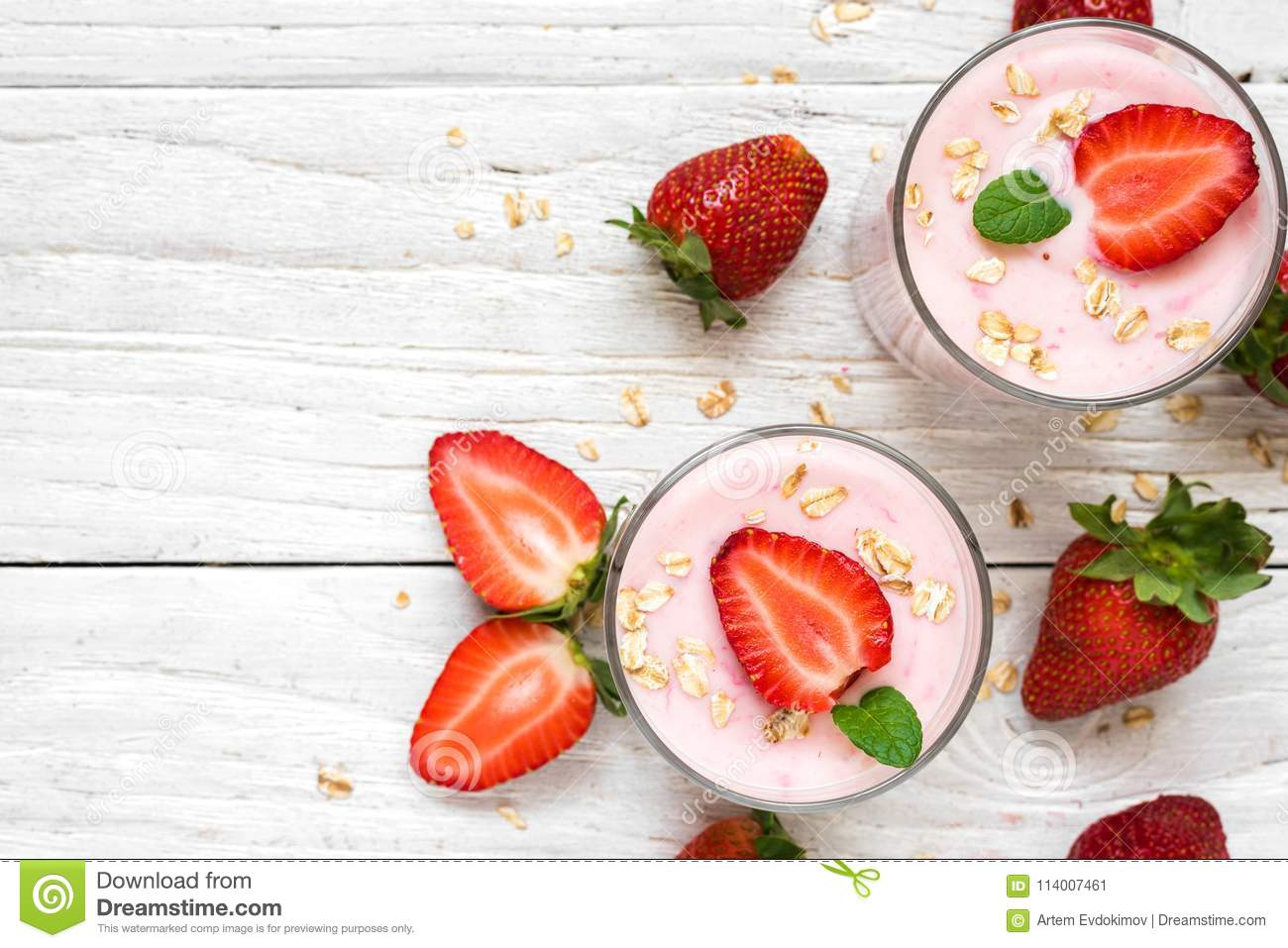 Healthy strawberry yogurt with oats and mint in glasses with fresh berries over white wooden table