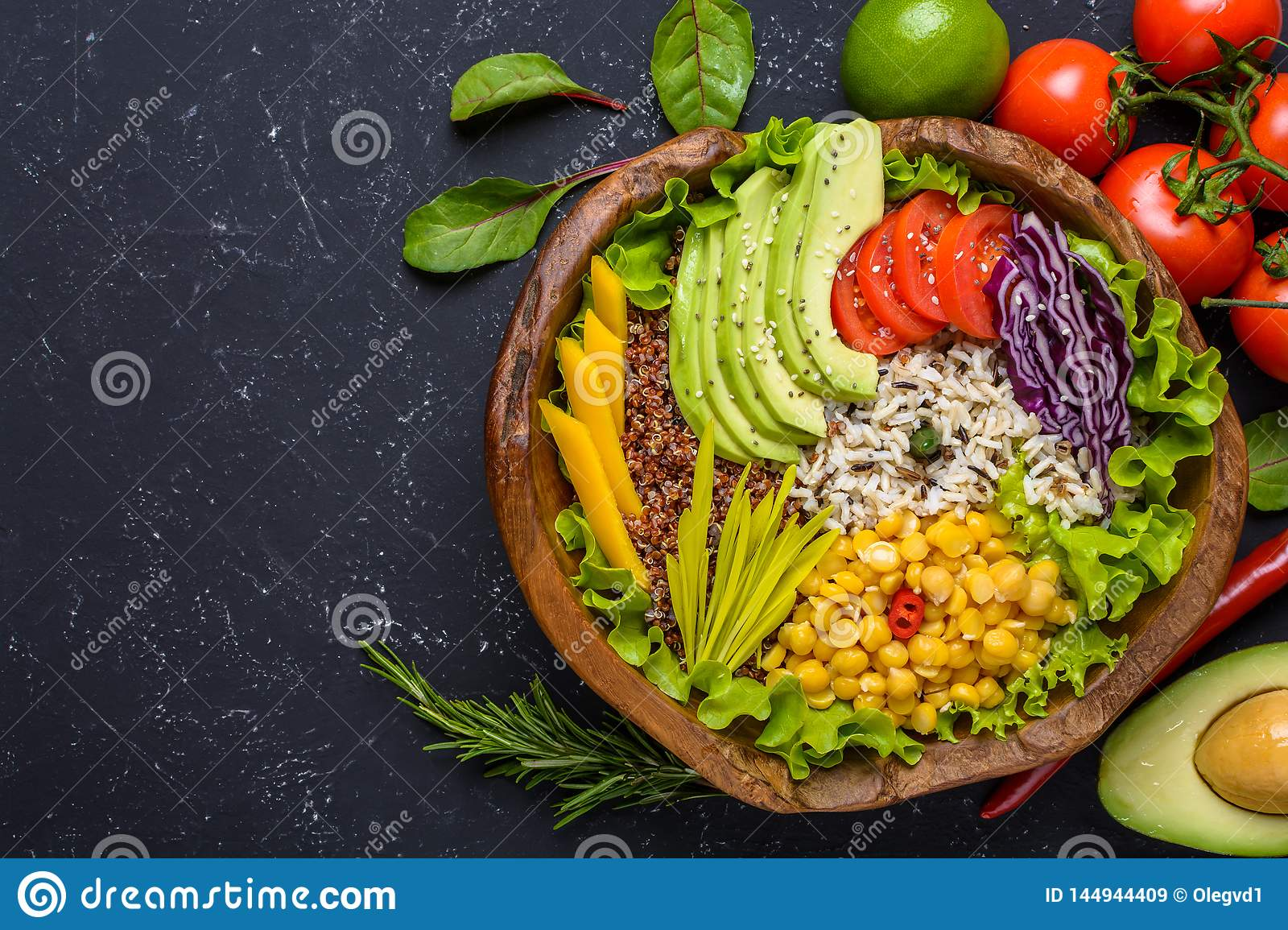 Healthy vegan food bowl with quinoa, wild rice, chickpea, tomatoes, avocado, greens, cabbage, lettuce on black stone background