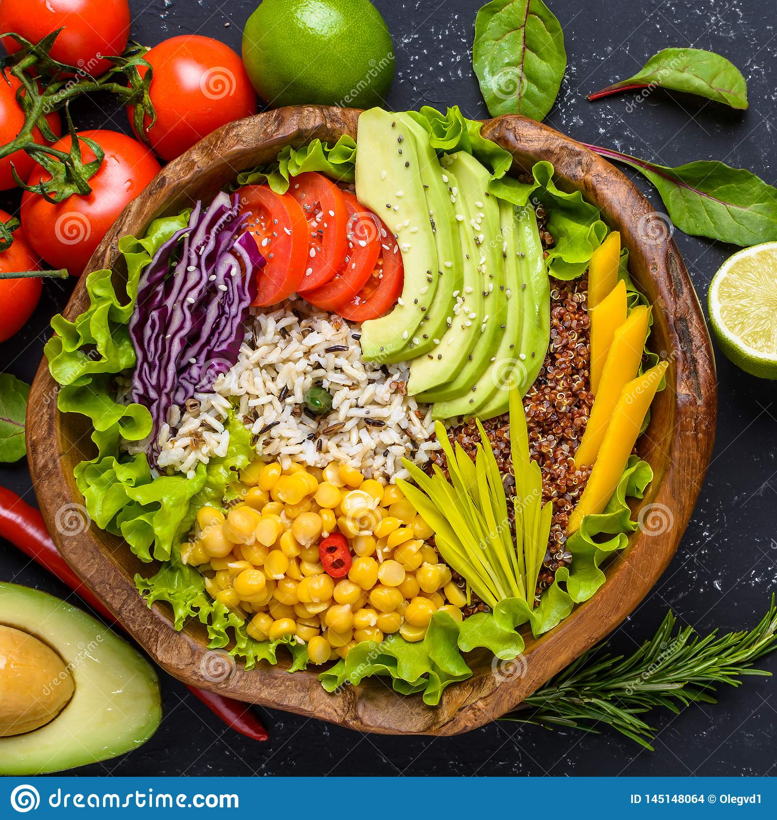 Healthy vegan superfood bowl with quinoa, wild rice, chickpea, tomatoes, avocado, greens, cabbage, lettuce on black stone