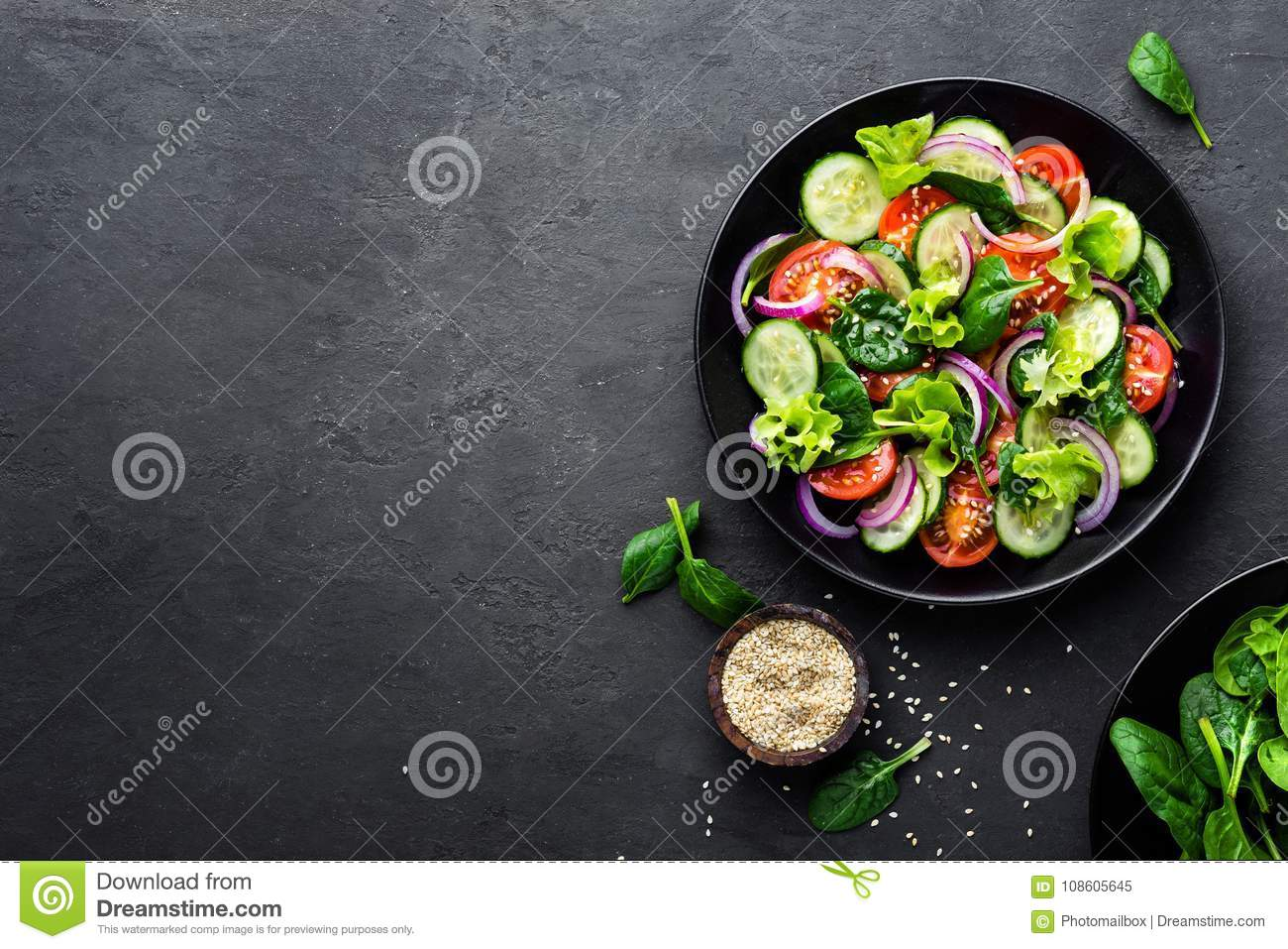 Healthy vegetable salad of fresh tomato, cucumber, onion, spinach, lettuce and sesame on plate. Diet menu