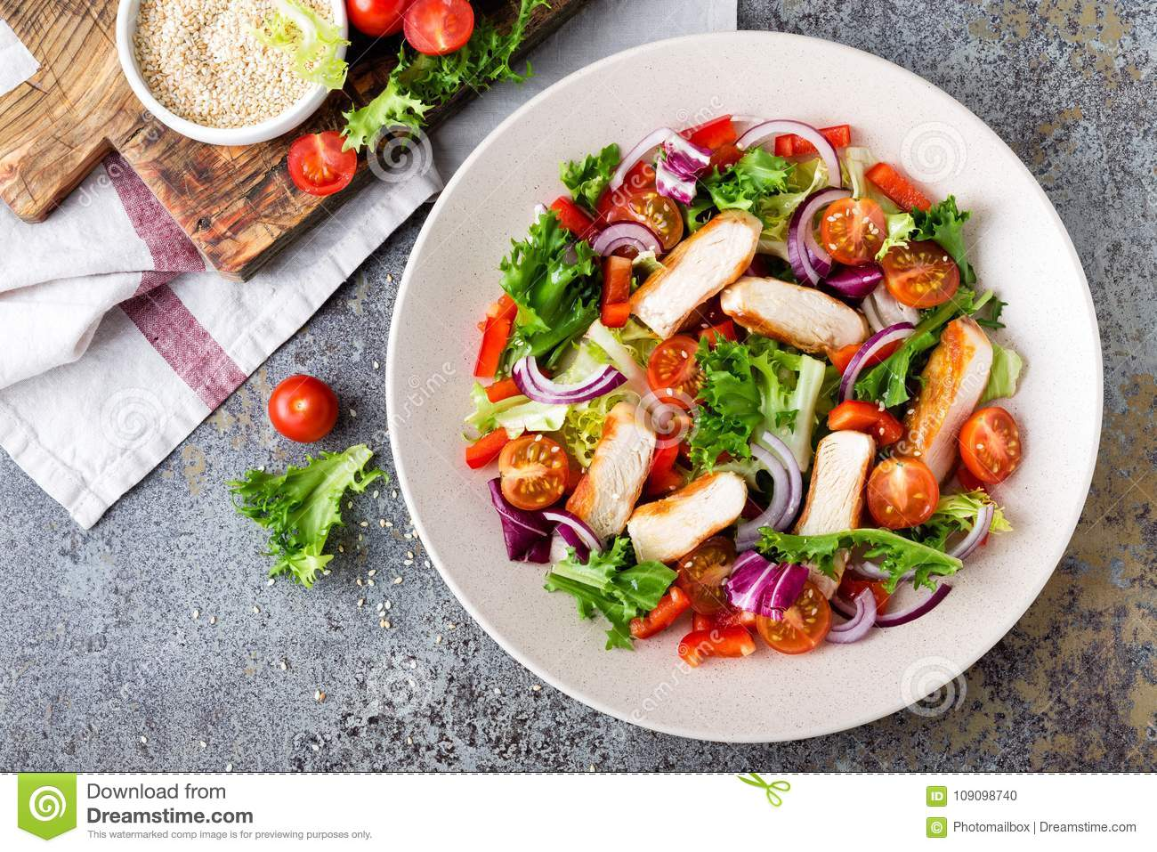 Healthy vegetable salad with grilled chicken breast, fresh lettuce, cherry tomatoes, red onion and pepper