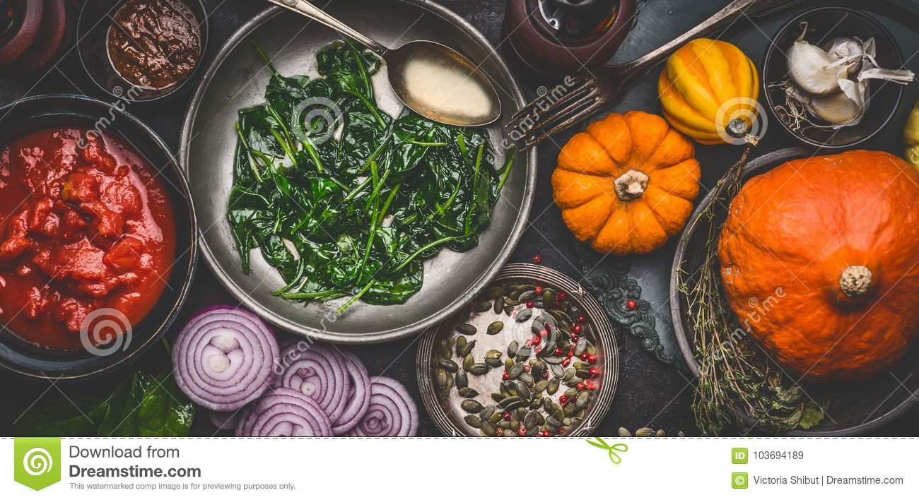 Healthy vegetarian cooking ingredients for tasty pumpkin dishes recipes in bowls : tomato sauces, spinach, sliced onion, pumpkin s