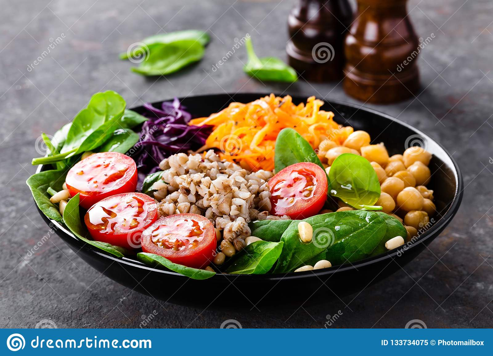 Healthy vegetarian dish with buckwheat and vegetable salad of chickpea, kale, carrot, fresh tomatoes, spinach leaves and pine nuts