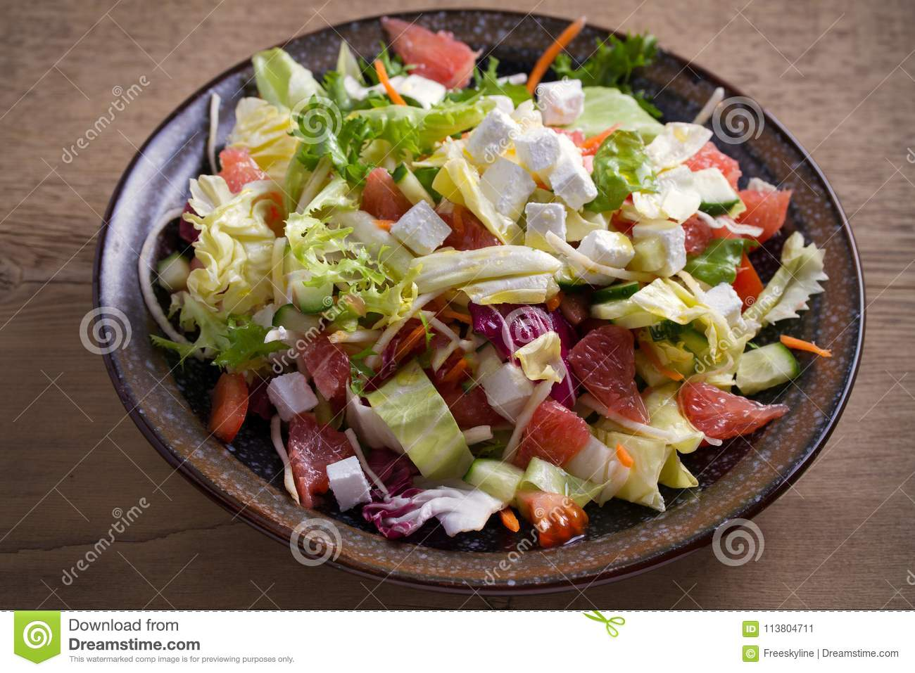 Healthy vegetarian food: citrus grapefruit, tomato, lettuce and cucumber salad with feta cheese in bowl on wooden table.