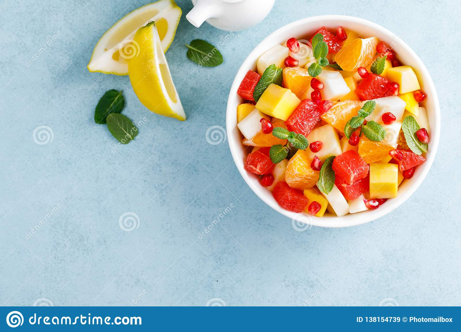Healthy vegetarian fresh fruit salad with apple, pear, tangerine, grapefruit, mango, pomegranate and lemon juice. Top view