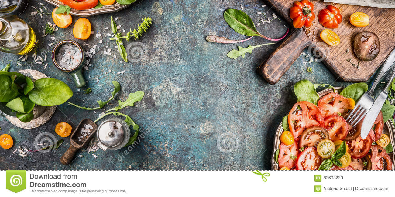 Healthy vegetarian salad making preparation with tomatoes on rustic background, top view