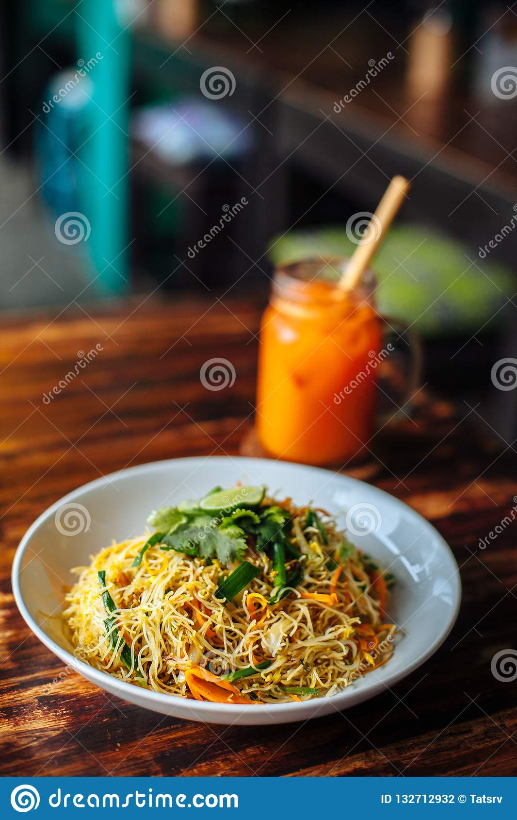 Healthy Vegetarian vegan menu Delicious Singapore style Stir fried rice noodles with carrot orange smoothies on wooden table in