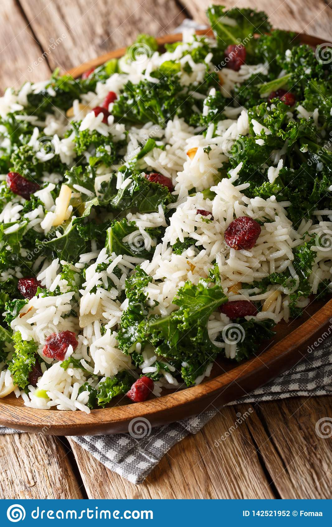 Healthy vitamin Kale with rice and cranberries close-up on a plate. vertical