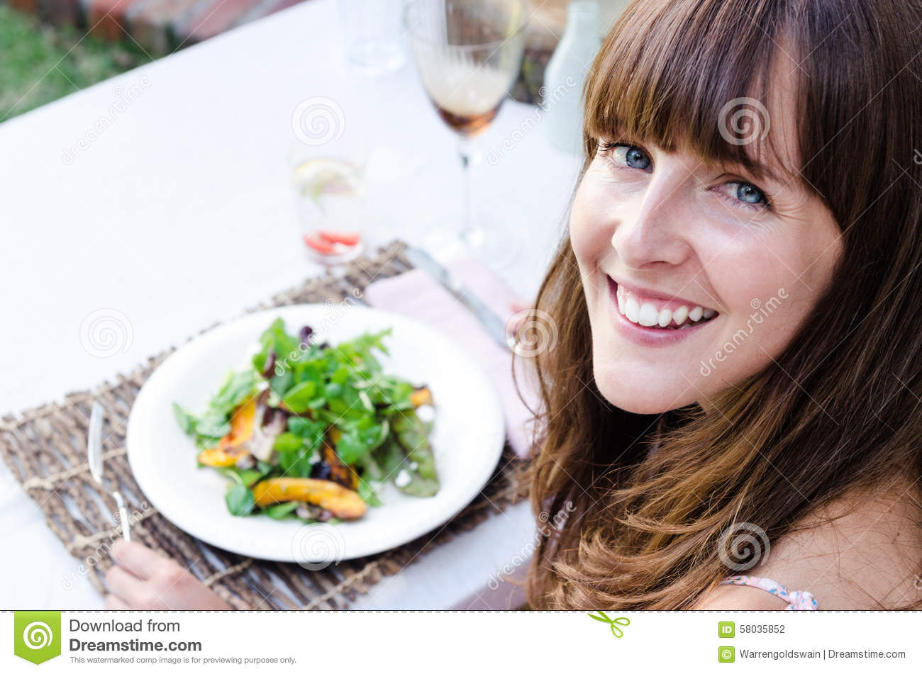 Healthy woman eating salad outdoors