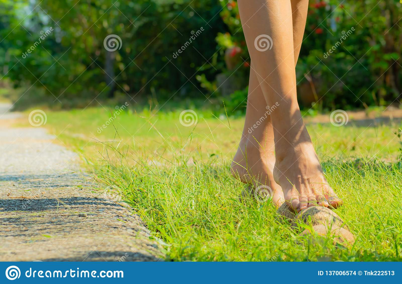 Healthy woman walking on the coconut shell or ka -la spa in front of her garden at home, self-care by herself, easy healthcare .