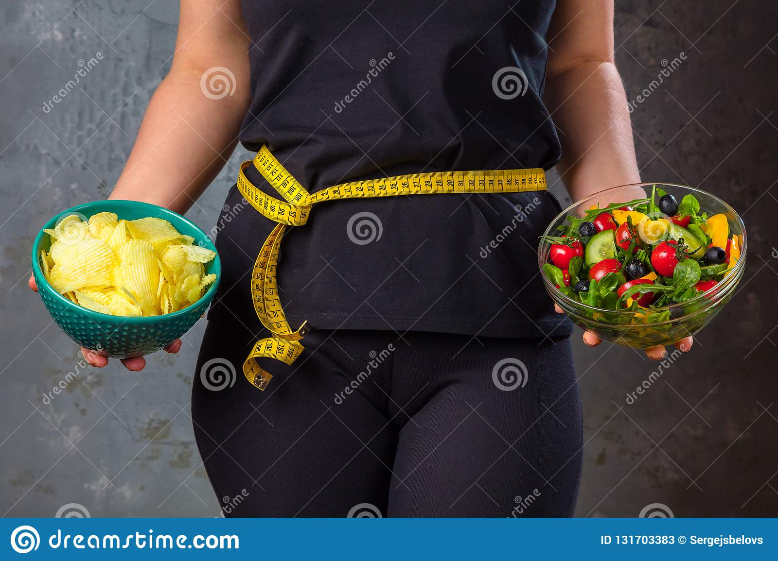 Healthy young woman looking at healthy and unhealthy food, trying to make the right choice