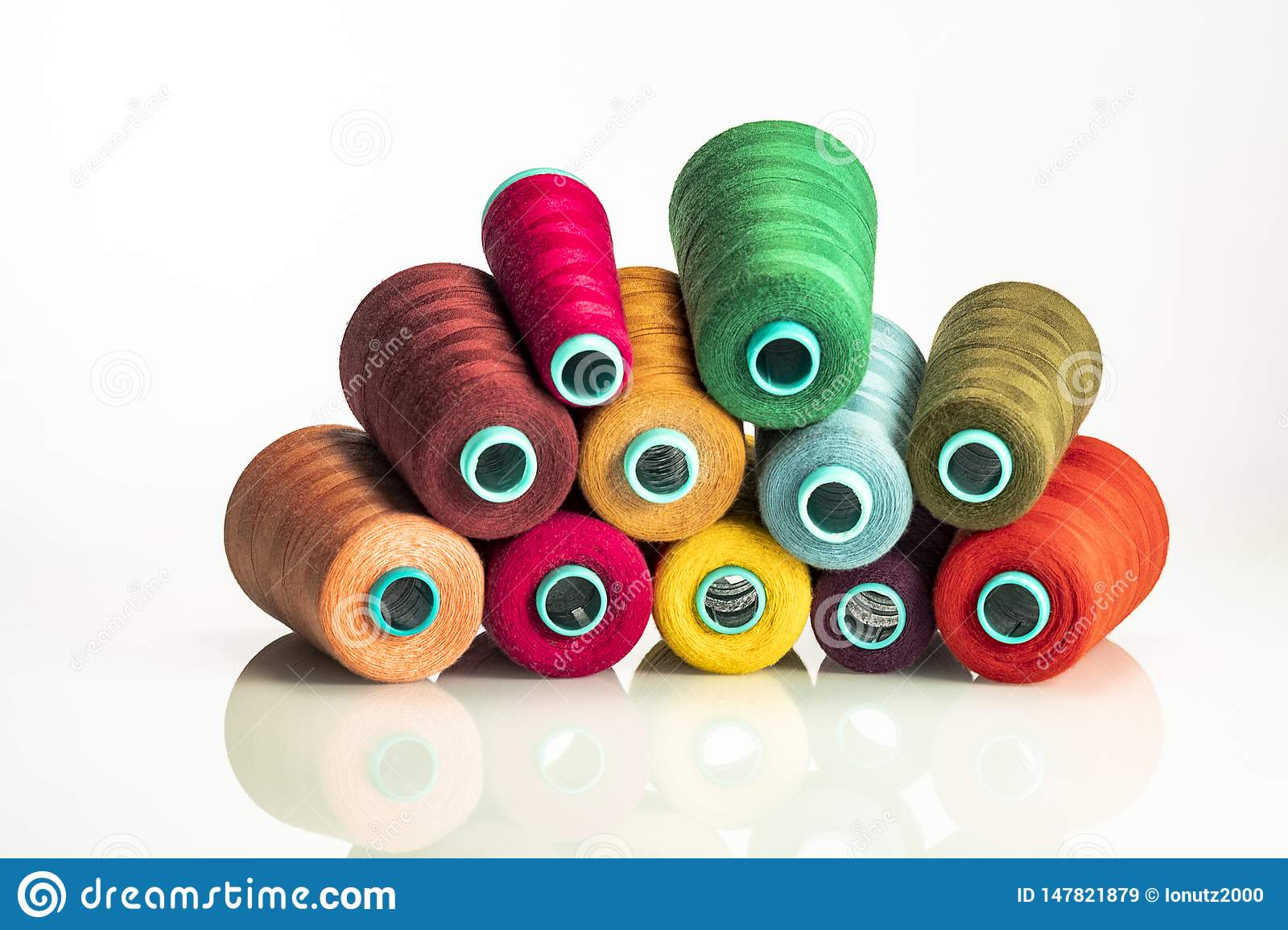 Heap colored industrial spools arranged on white background