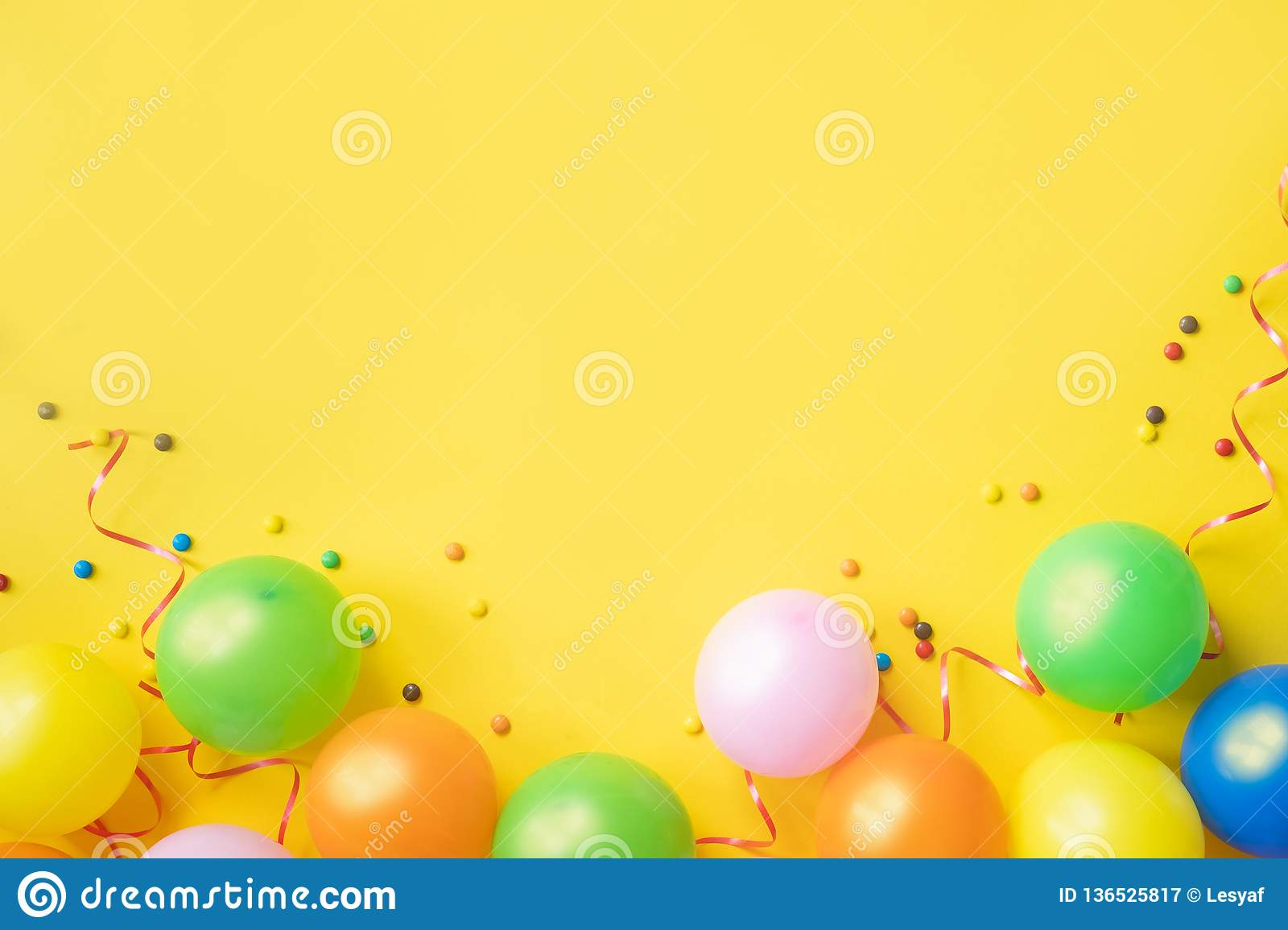 Heap of colorful balloons, confetti and candies on yellow table top view. Birthday party background. Festive greeting card