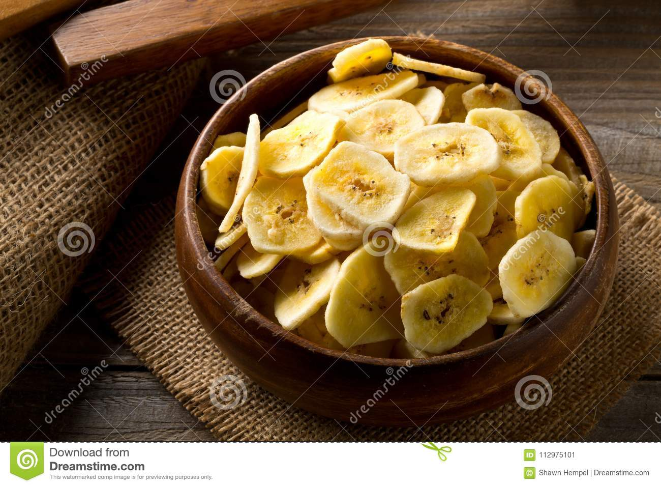 Heap of dried banana chips snack in wooden bowl on dark table