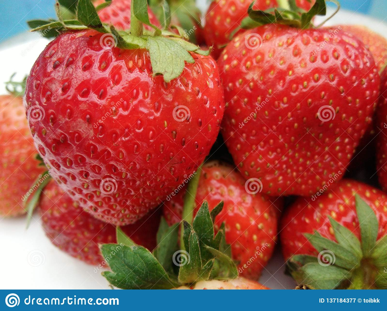 Heap of fresh ripe strawberry fruit with green sepal