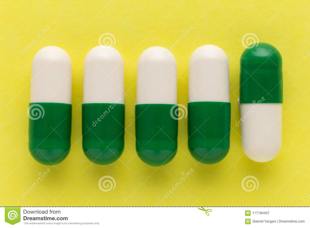 heap of white and green capsules on white background pills are