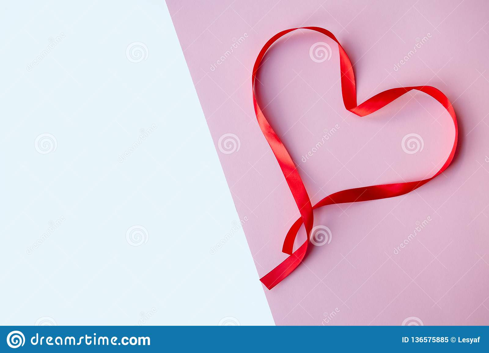 Heard red silk ribbon , on pink and white background. Mother`s, Women`s, Wedding, Happy st Valentines Day concept, 14th Fe