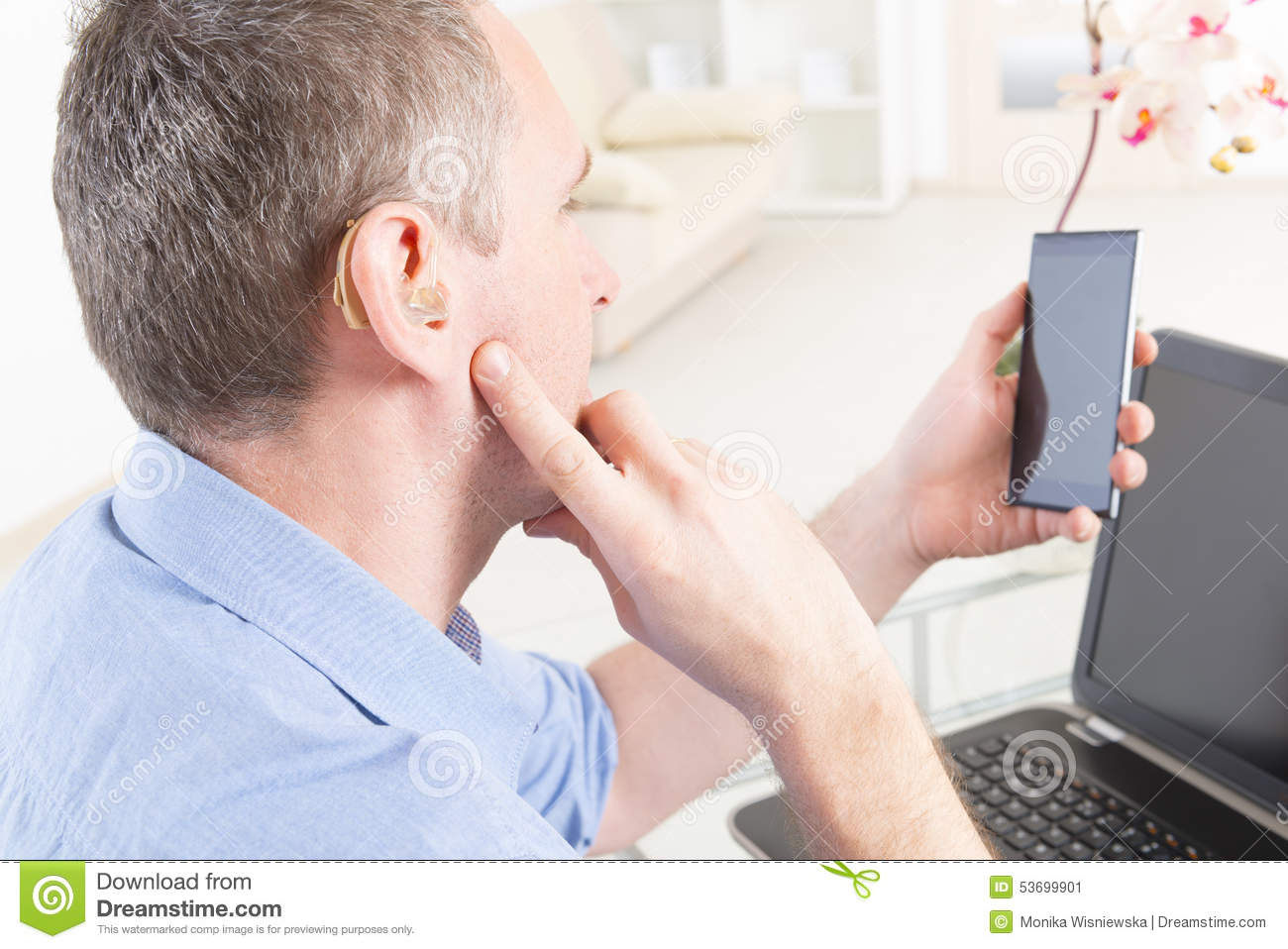 hearing impaired man working with laptop and mobile phone