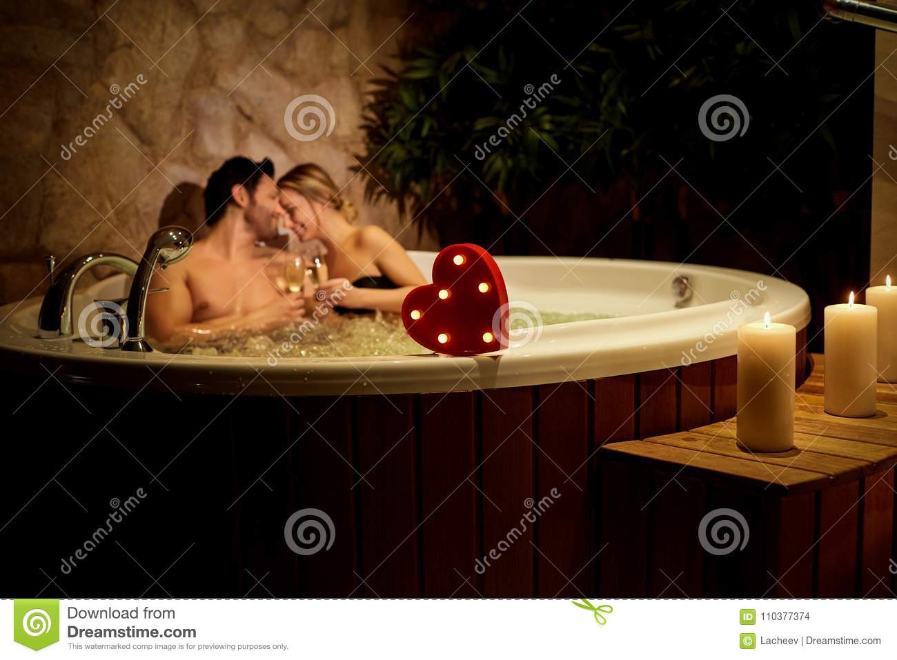 Heart on a background of a romantic couple with champagne in the